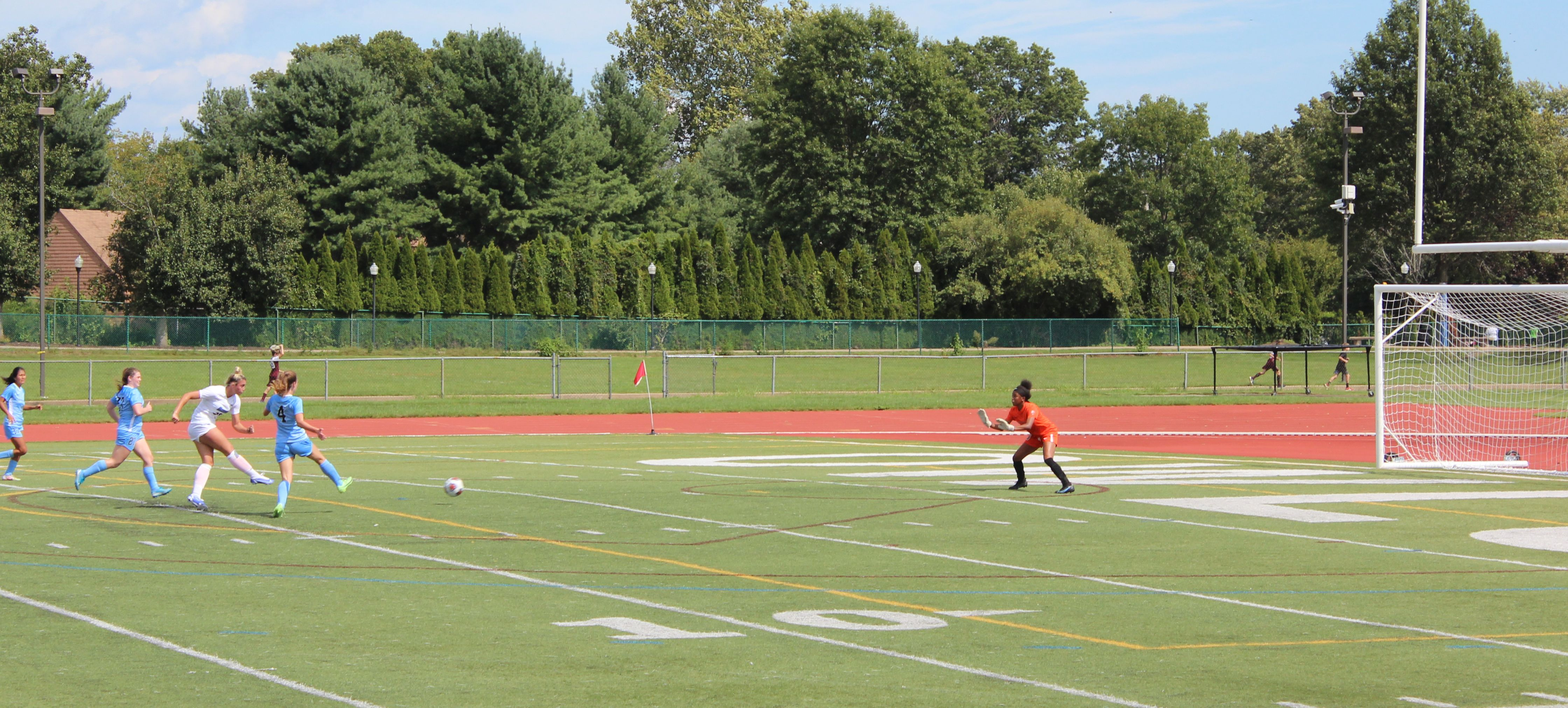 A SCSU player in white kicks the ball flanked by two light blue glad defenders at a red clad goalkeeper.