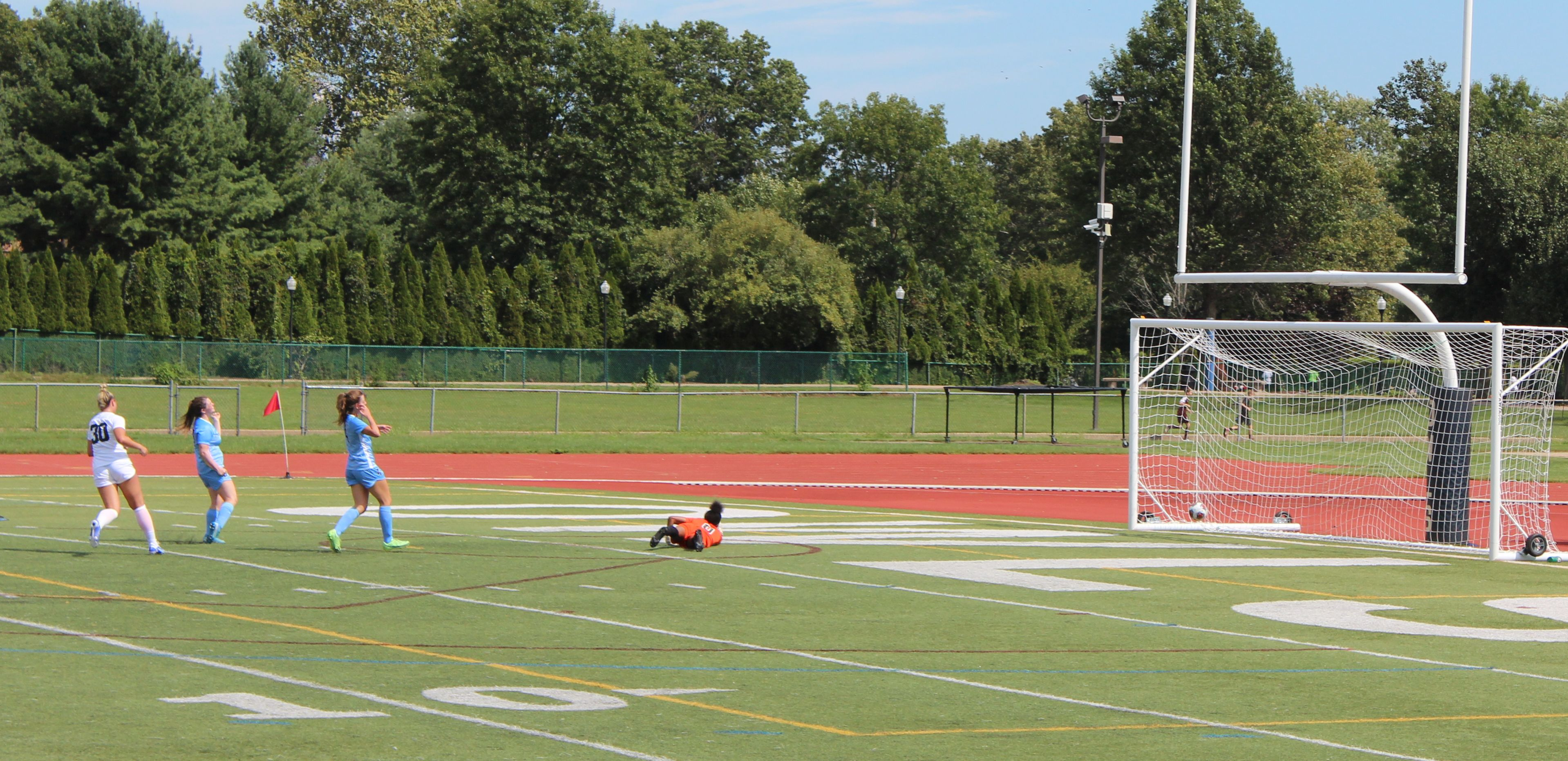 The soccer ball goes into the net past a sprawled red clad goaltender as a SCSU player in white who shot it and 2 blue clad defenders look on.